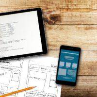 tablet cellulare e schema per creazione di un sito web cartaceo su un tavolo di legno