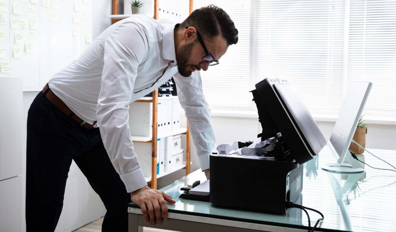 ragazzo controlla un guasto alla stampante