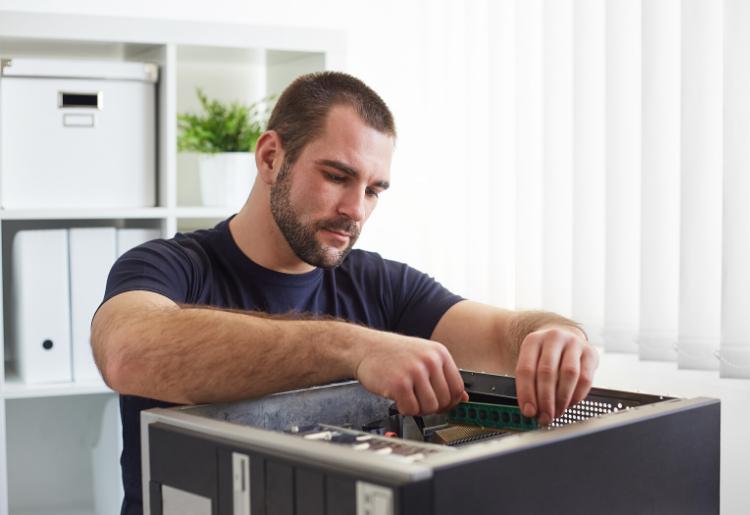 Tecnico informatico al lavoro su un computer